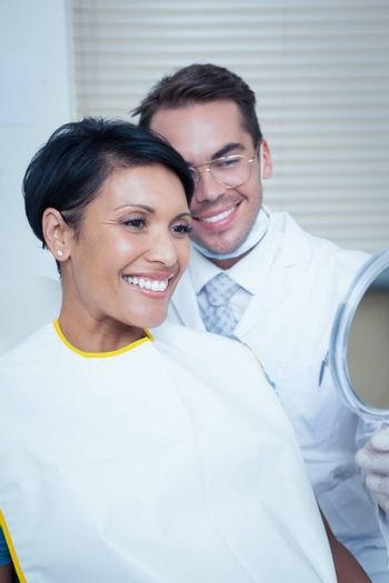Smiling young woman looking at mirror in the dentists chair