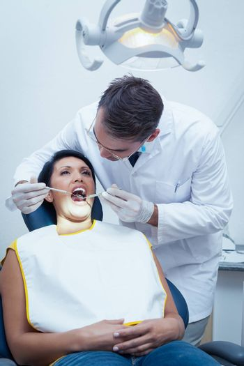 Male dentist examining womans teeth in the dentists chair