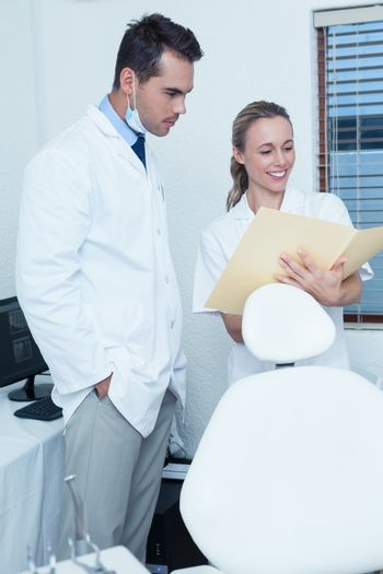 Smiling female and male dentists discussing reports