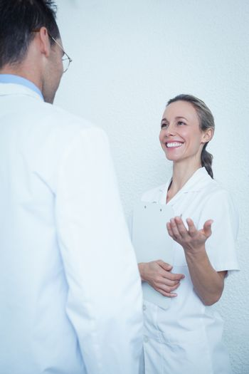 Smiling female and male dentists in discussion