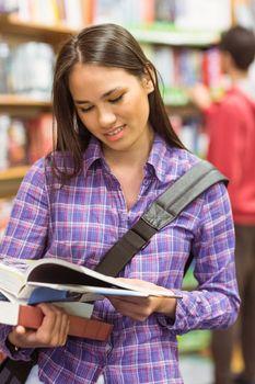 Smiling university student reading textbook