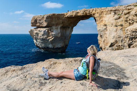 Girl looking on Azure Window formation on Gozo Island
