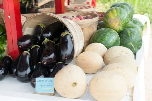 Fresh melons for sale at a farm stand along with some fresh eggplants.  Shallow depth of field.