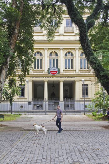 SAO PAULO, BRAZIL - MARCH 8, 2015: An unidentified man walking with a dog in front of Centro Paula Souza University in  Sao Paulo Brazil.