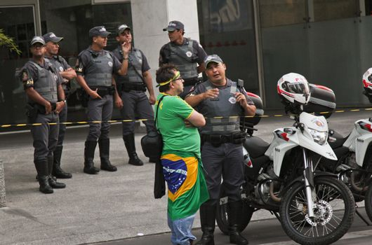 SAO PAULO, BRAZIL - APRIL 12, 2015: An unidentified man talking with a police man at protest against federal government corruption in Sao Paulo Brazil. Protesters call for the impeachment of President Dilma Rousseff.