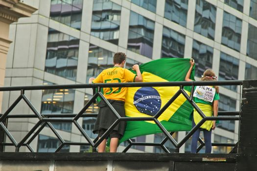 SAO PAULO, BRAZIL - APRIL 12, 2015: Two unidentified kids with brazilian flag at protest against federal government corruption in Sao Paulo Brazil. Protesters call for the impeachment of President Dilma Rousseff.