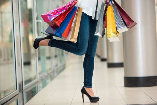 Woman legs with shopping bags against the backdrop of a shopping center