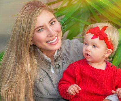 Portrait of beautiful mother with cute little daughter having fun in fresh green park, happy young family enjoying spring season