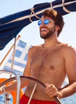 Happy guy behind wheel of sailboat