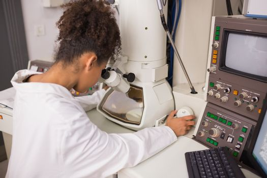 Biochemistry student using large microscope and computer