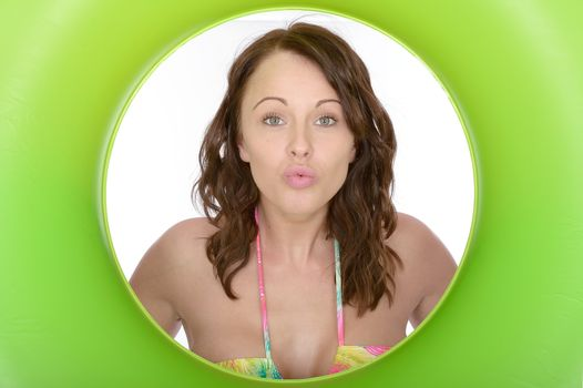 Attractive Young Woman Looking Through a Green Rubber Ring Blowing a Kiss