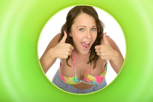 Attractive Young Woman Looking Through a Green Rubber Ring Giving Thumbs Up Sign