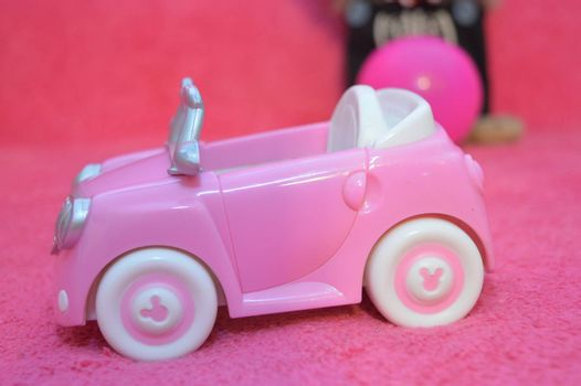 Pink children's toy car model on pink background