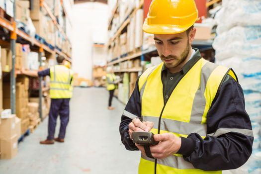 Focused worker wearing yellow vest using handheld