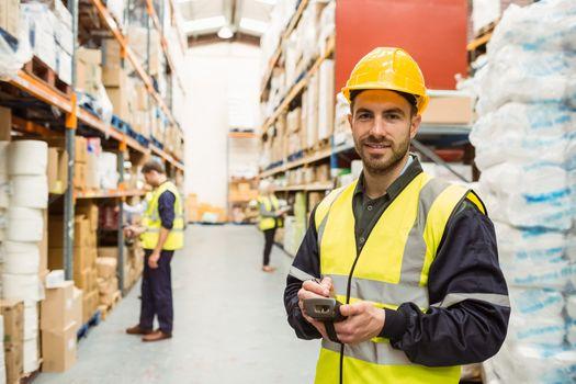 Smiling worker wearing yellow vest using handheld