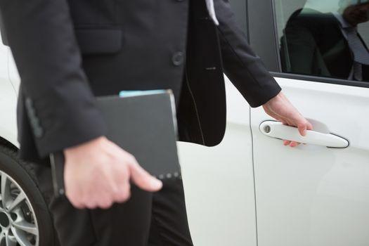 Businessman holding a car door handles