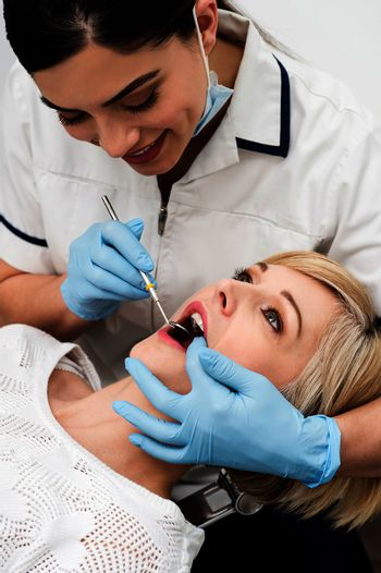 Female patient teeth checked by dentist