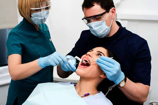 Male dentist treat the female patient mouth