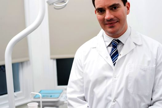 Male dentist posing with welcoming smile