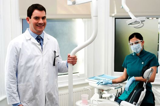 Male dentist and his female assistant posing