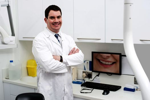 Happy dentist posing with computer screen