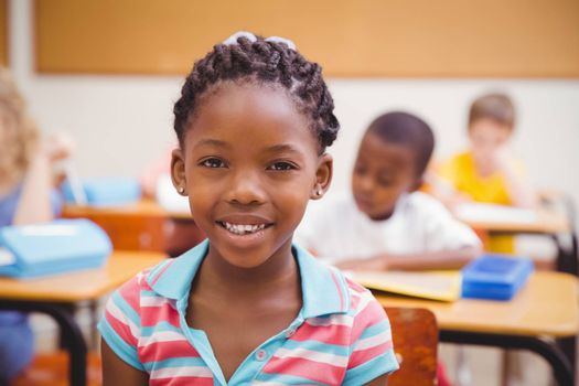 Smiling pupil sitting at her desk at the elementary school