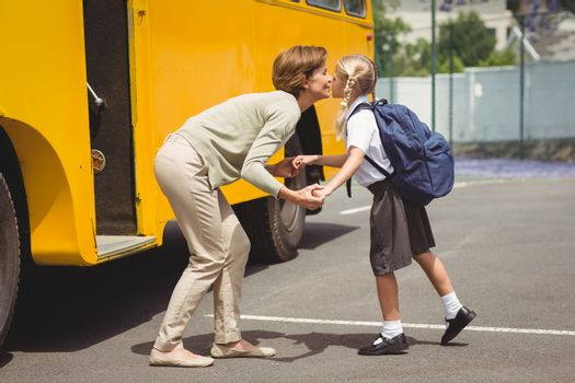 Mother kissing her daughter by school bus outside the elementary school