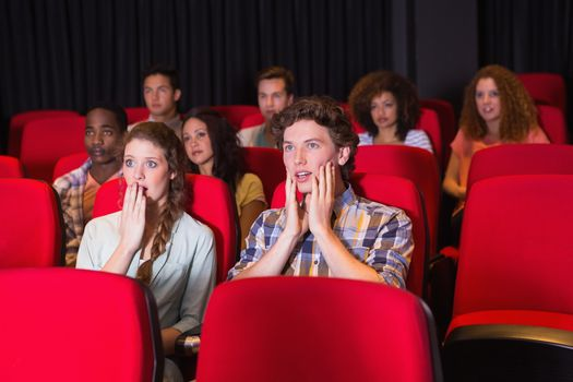 Surprised young friends watching a film