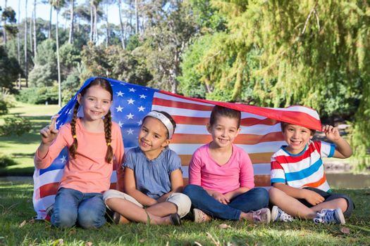Happy little friends with american flag on a sunny day