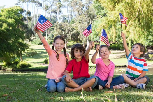 Happy little friends waving american flag