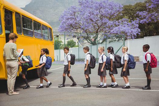 Cute schoolchildren waiting to get on school bus outside the elementary school