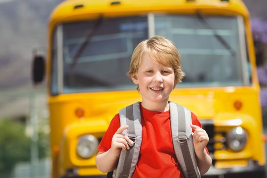 Cute pupil smiling at camera by the school bus outside the elementary school