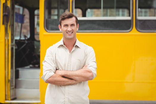 Smiling bus driver standing with arms crossed in front of his bus