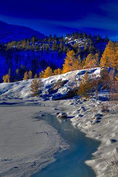 Sun shining over a winter landscape at sunset