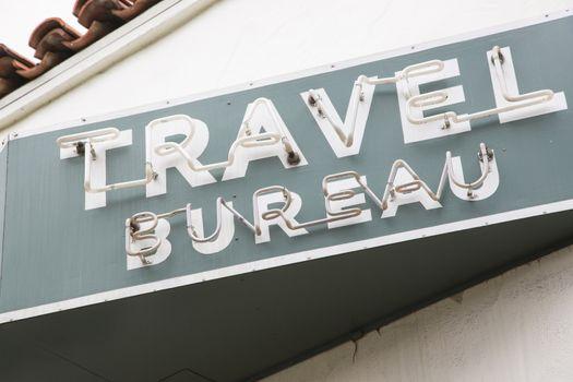 Neon Travel Bureau Sign on Building