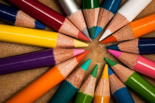 Colorful wooden pencils isolated on brown background
