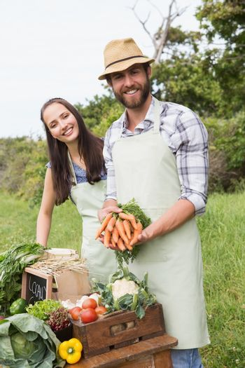 Couple selling organic vegetables at market