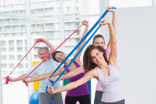Happy female friends exercising with resistance bands