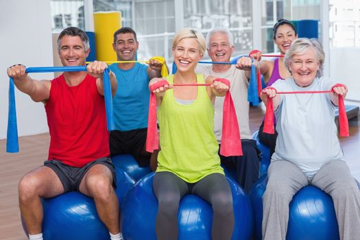 People exercising with resistance bands in gym class