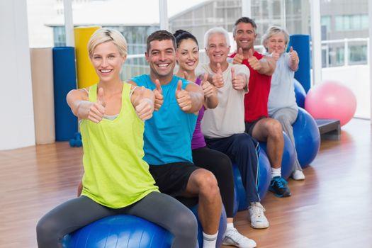 People gesturing thumbs up in health club