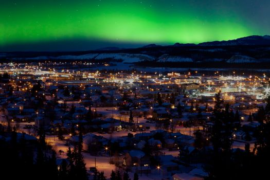 Strong northern lights (Aurora borealis) substorm on night sky over downtown Whitehorse, capital of the Yukon Territory, Canada, in winter.