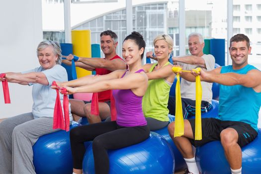 Happy people exercising with resistance bands in gym