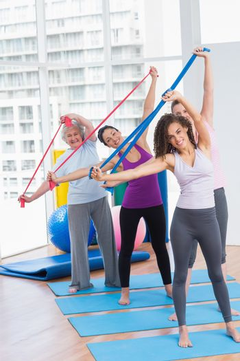 Happy friends exercising with resistance bands