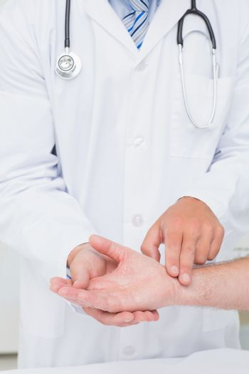 Doctor checking patients pulse rate