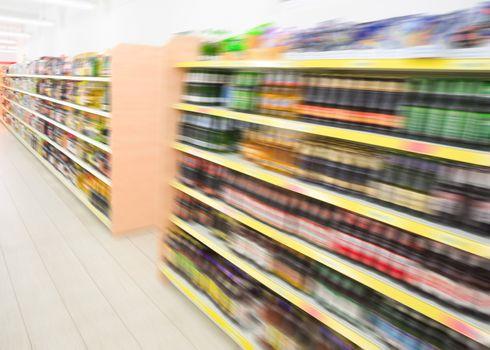 Shelves with beverages bottles in grocery food store supermarket