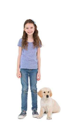 Smiling little girl standing next to dog on white background
