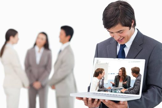 Salesman showing laptop screen with team behind him against attractive businesswoman laughing with her team