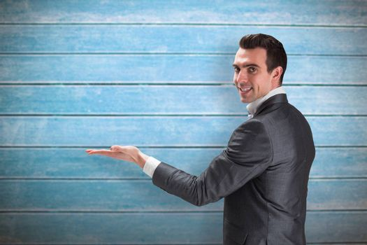 Businessman presenting with hand against wooden planks
