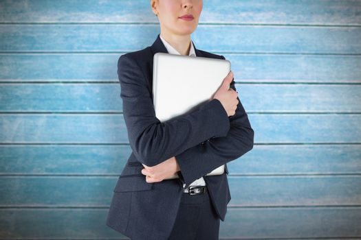Businesswoman holding laptop against wooden planks