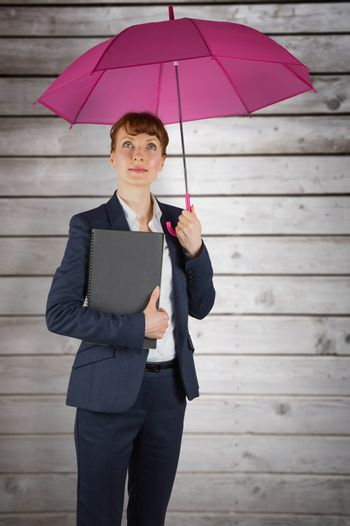 Businesswoman with umbrella against wooden planks